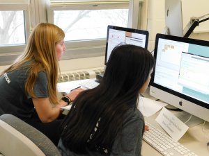 Two female students from Middletown High School South facing their computers at the competition
