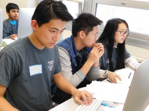 2 male students and 1 female students focused and working on writing programs at the competition with pens and papers on their desks