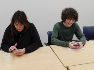 High School teacher Susanne Signorelli and student sitting at table and looking at their phones