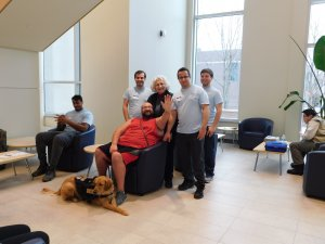 5 male students, one with a golden retriever service dog, and professor smiling for the camera