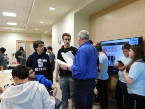 2 male students talking with their high school programming teacher, as other contestants and MU students stand nearby.