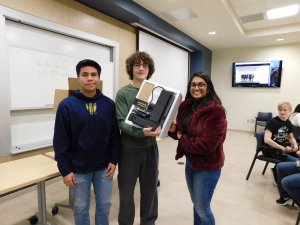 3 students (2 males and 1 female) holding up a 3D printer they each won for 1st place in the Monmouth University High School Programming Contest