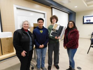 3 students (2 males and 1 female) with MU Professor Kretsch holding up a 3D printer they each won for 1st place in the Monmouth University High School Programming Contest