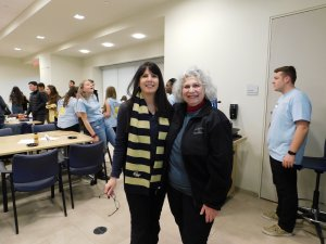 MU Professor Kretsch standing with Ms. Corrado from Toms River and smiling as male and female students move in the background