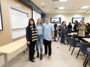2 Monmouth University student volunteers, 1 a male and 1 a female smiling and standing alongside their female teacher from Toms River North high school Ms. Corrado