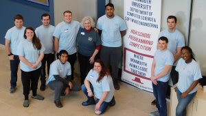 a group of 7 males and 3 female Monmouth University student volunteers with professor Kretsch. The group is posing in front of a banner for the 2019 High School Programming Competition