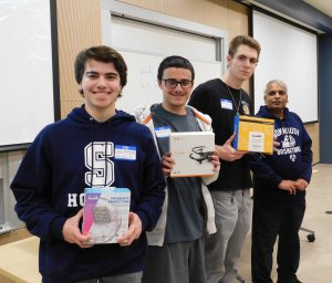 3 male students and sponsor Dr. Lakshmanan. Students are holding prizes won for 3rd place in Monmouth University High School Programming contest 2019