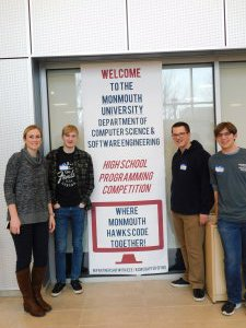 1 female MRHS teacher and 3 male students next to the HSPC banner (Welcome to the Monmouth University Dept of Computer Science & Software Engineering High School Programming Competition - Where Monmouth Hawks Code Together)