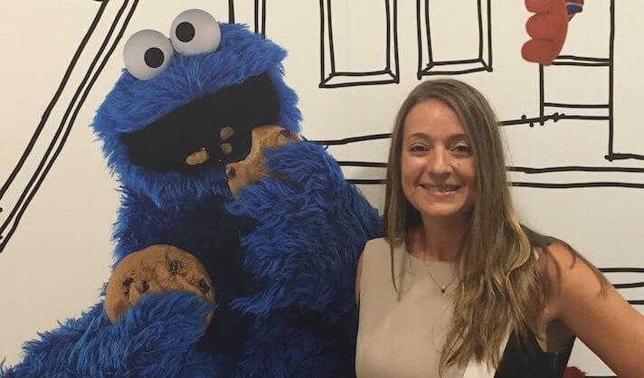 Psychology professor Lisa Dinella alongside Sesame Street's Cookie Monster