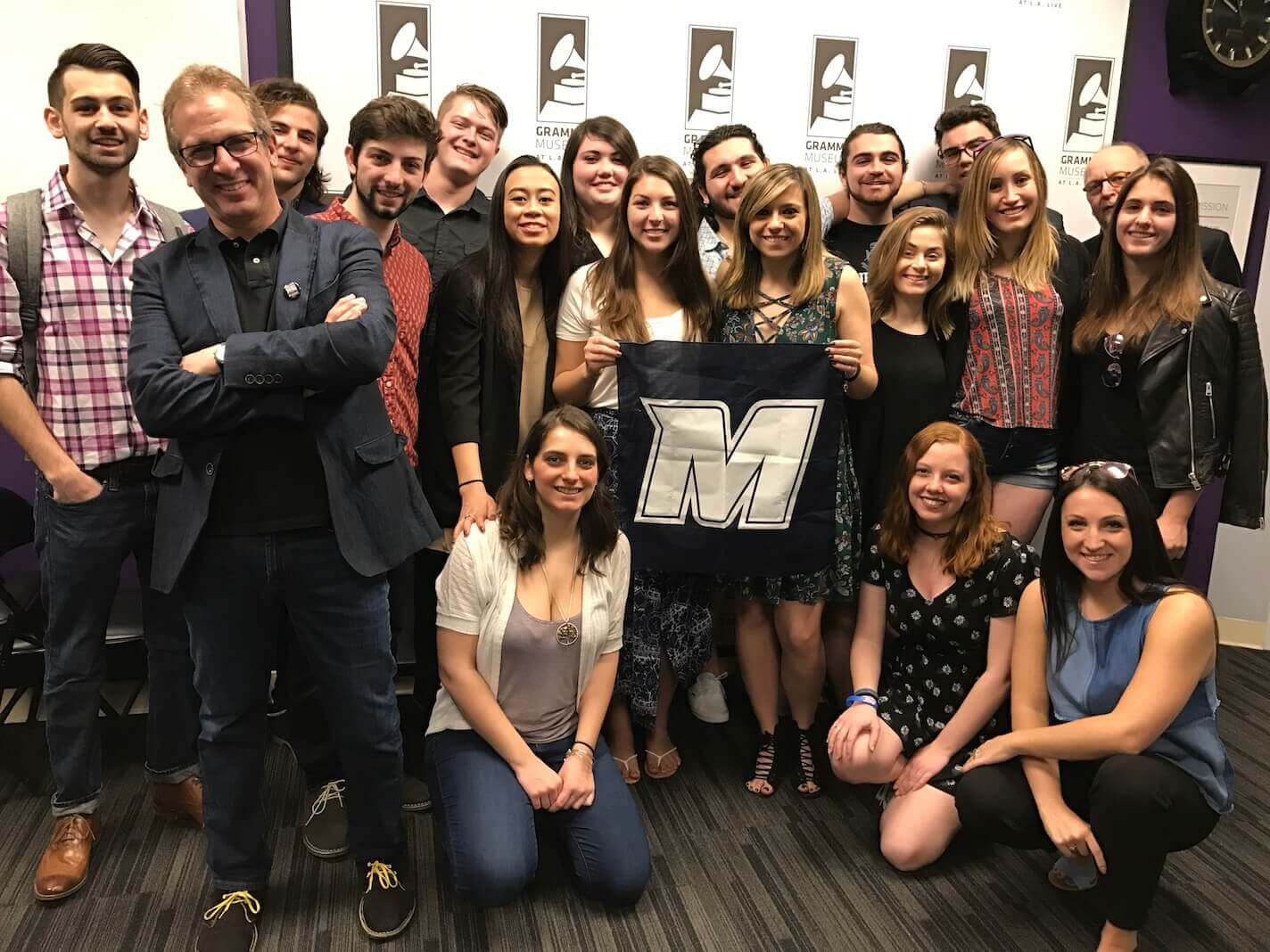 Students and faculty from the university's Music, Communications, and Business programs, standing together for a group photo in the Grammy Museum at L.A. Live