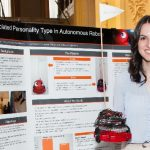Click to View 2015 Student Research Conference Photo of Jessica Kostiou with robots
