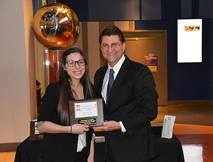 Photo of Nicole R Famularo receiving the Outstanding Presentation Award during the 2014-2015 Undergraduate Research Symposium of the Independent College Fund of New Jersey