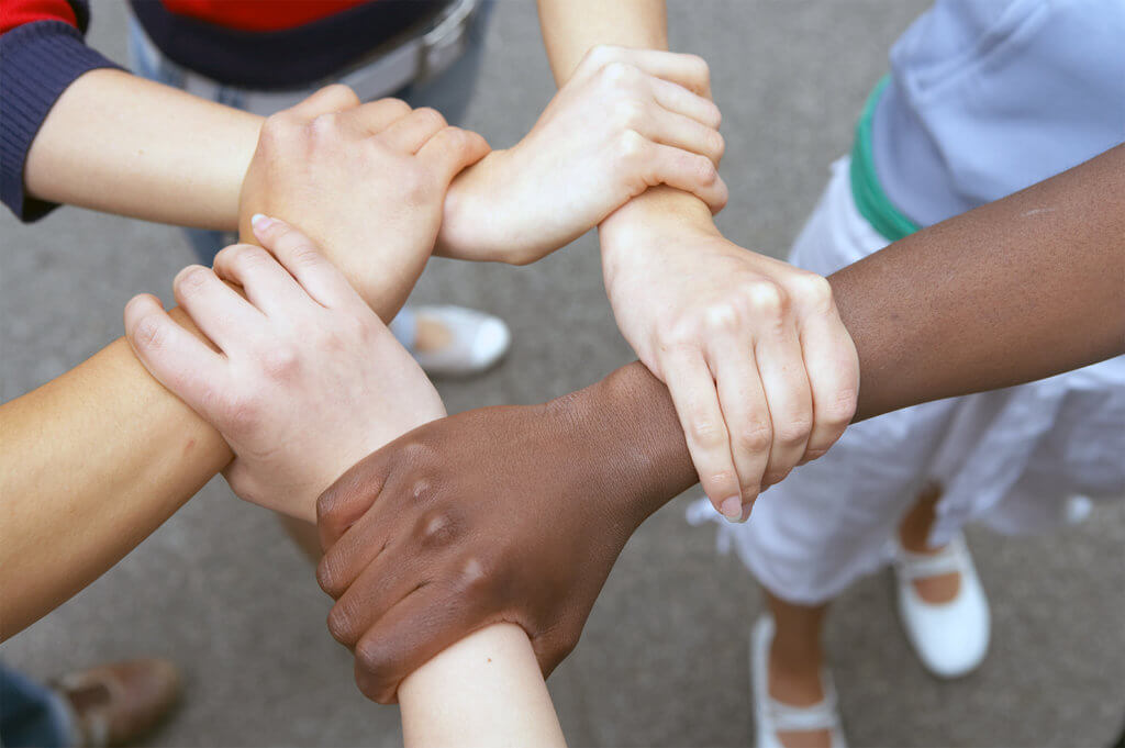 Photo shows 4 multi-racial arms joined together