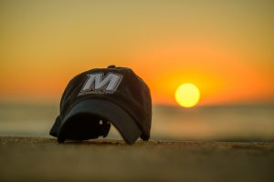 Photo of Monmouth University cap sitting on the beach at West Long Branch NJ at sunrise