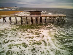 Photo shows storm waves breaking against pier at the beach