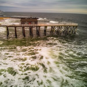 Photo of storm waves along beach pier