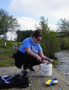 A student bending over a sample buck near a body of water.