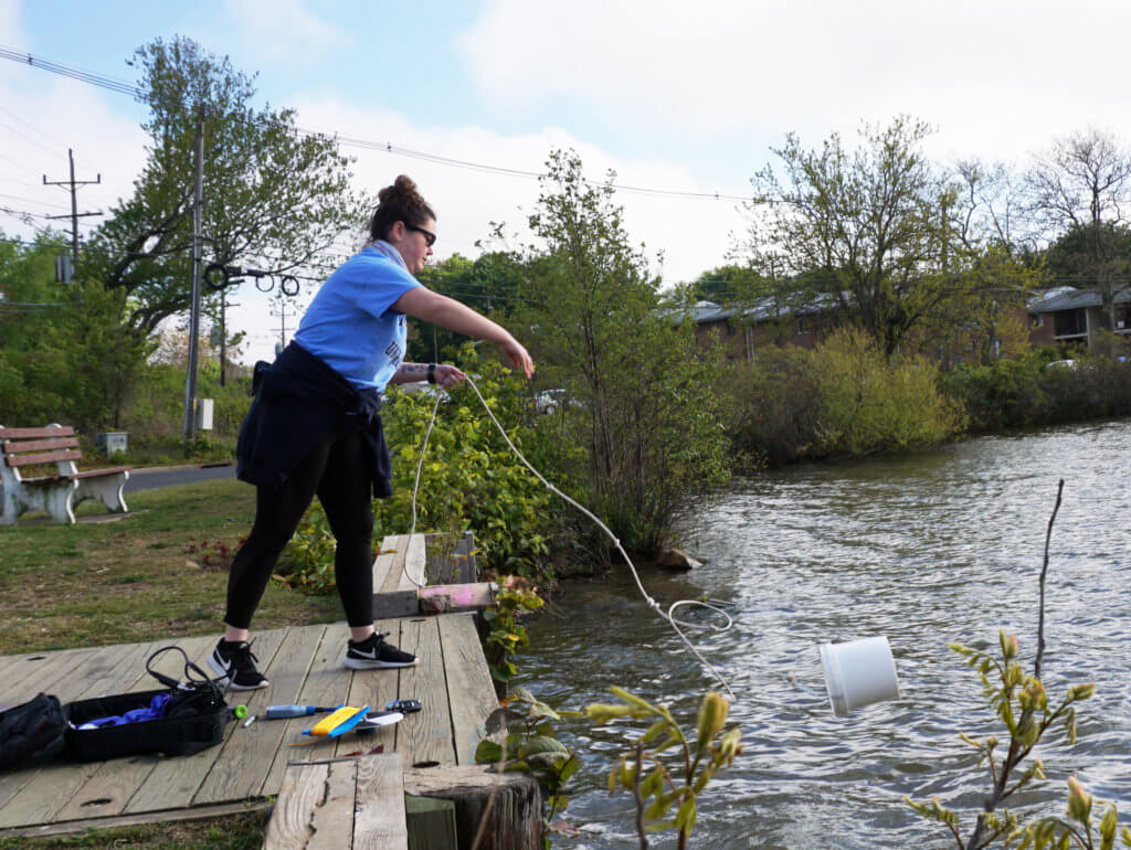 A woman throwing a sample bucked into a body of water
