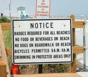 Photo image of boardwalk notice of beach badge requirements along with rules and regulations.