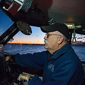Photo of Jim Nickels piloting a boat.